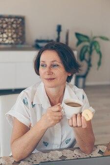 コーヒーを飲みながら家で少し笑顔で日中思慮深く見て白いシャツの年上の女性