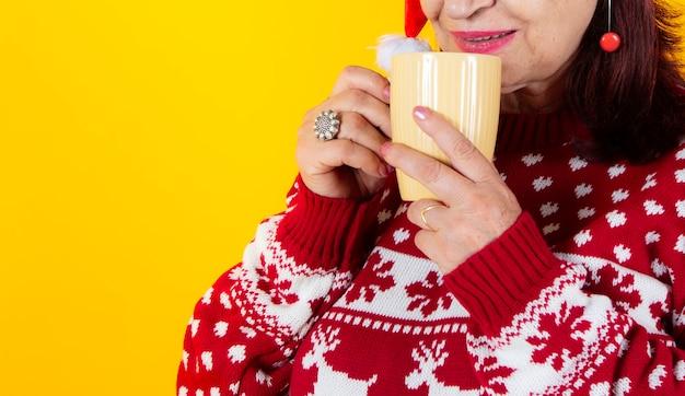 伝統的なクリスマスマグカップで横になっている年上の女性。サンタクロースの帽子