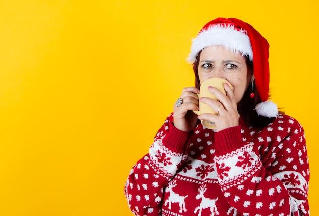 Older woman laying down with a traditional christmas mug. santa claus hat