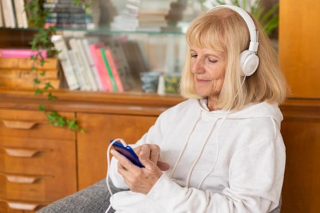 Пожилая женщина слушает музыку дома с помощью смартфона и наушников