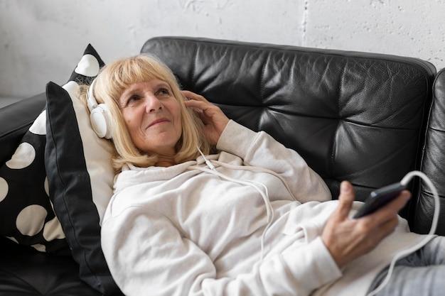 Пожилая женщина на диване, слушает музыку в наушниках