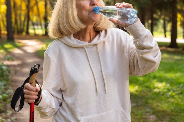 Пожилая женщина на открытом воздухе пьет воду во время треккинга