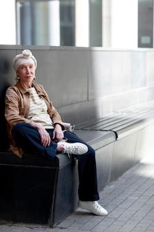 ベンチに座って街の屋外で年上の女性