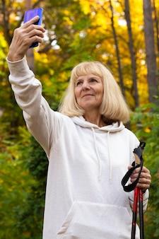 Donna anziana all'aperto prendendo selfie durante il trekking