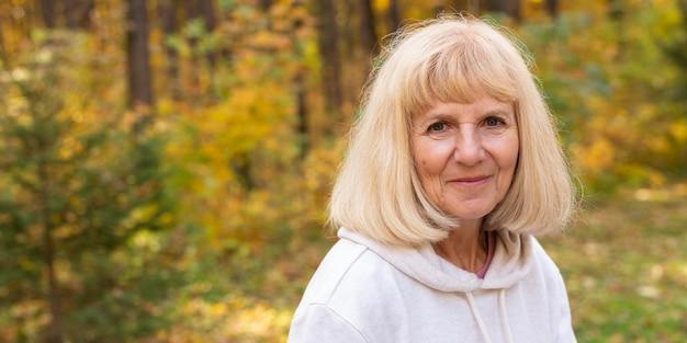 Пожилая женщина позирует на открытом воздухе на природе