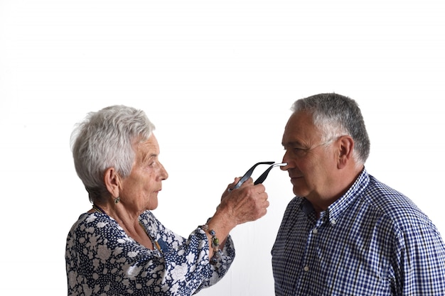 An older woman putting on glasses to an older man