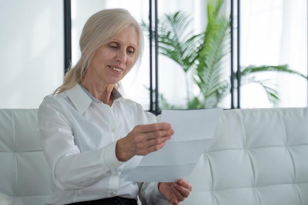 거실 소파에 앉아 편지를 읽는 나이든 여성은 안경을 쓴 성숙한 여성이 편지에서 좋은 소식을 읽고 기뻐한다