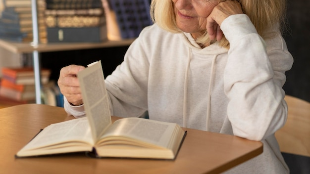 Пожилая женщина читает дома