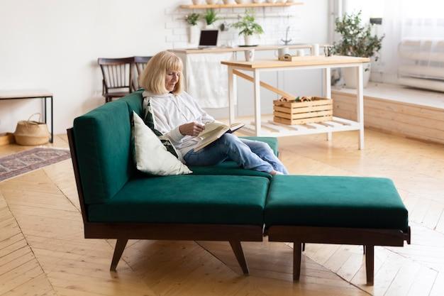 Donna anziana che legge un libro a casa sul divano