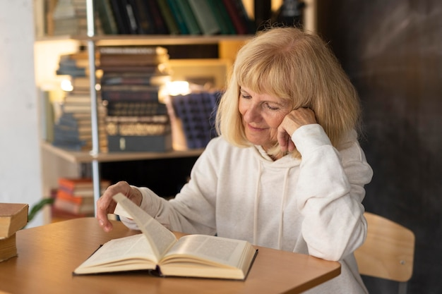 Donna anziana che legge un libro a casa