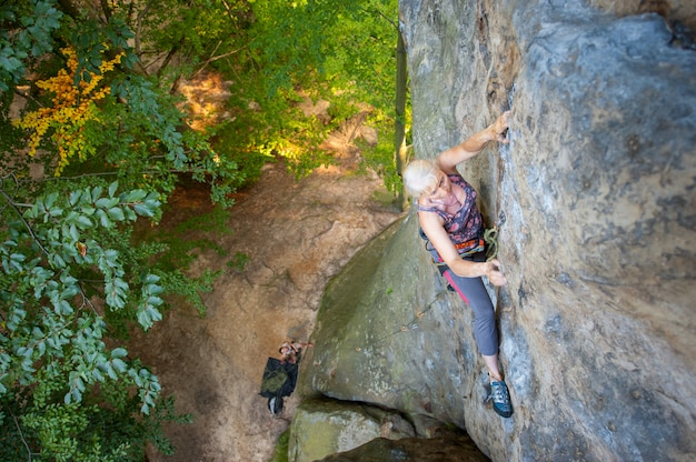 Older woman rock climber is climbing on a rocky wall