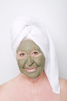나이 든 여자의 웃는 얼굴, 수건 및 점토 마스크