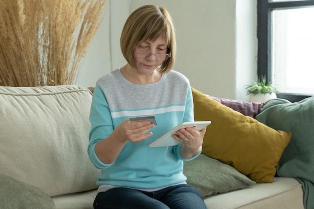 Пожилая женщина делает покупки в интернете с помощью кредитной карты с помощью цифрового планшета