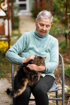 Donna anziana seduta su una sedia e accarezzare il gatto