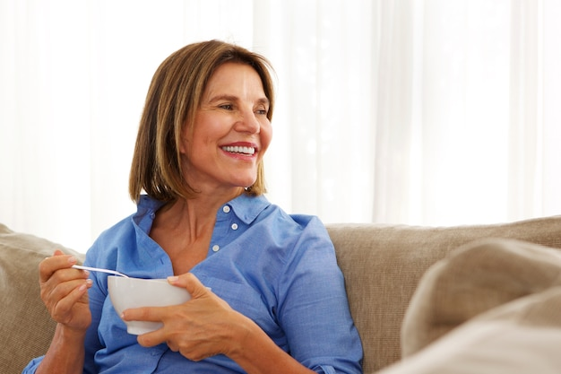 Older woman sitting at home with bowl of breakfast