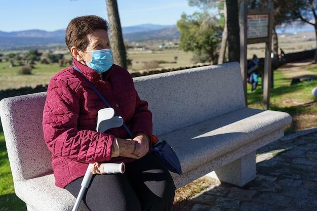 노인 여성이 코로나 바이러스로 인해 사회적 거리를두고 공원 벤치에 앉아 있습니다.