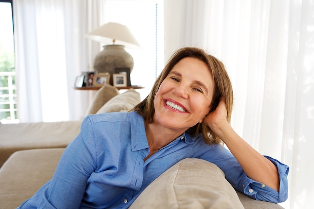 Older woman smiling at home on sofa