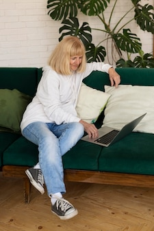 Older woman on the sofa at home with laptop