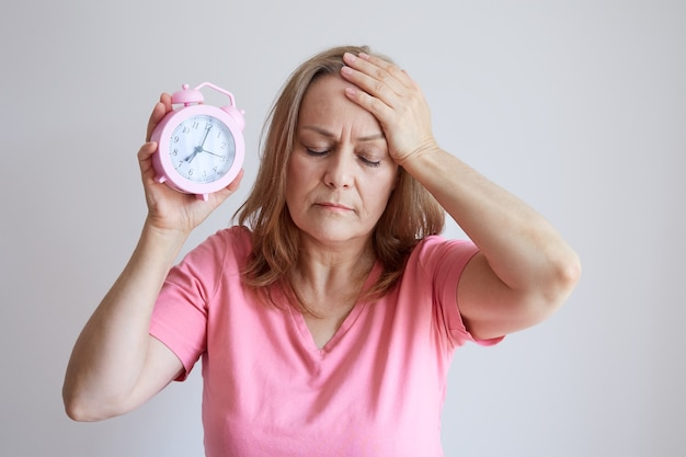 Older woman suffers from insomnia, headache, holds an alarm clock in her hand. photo on gray background.