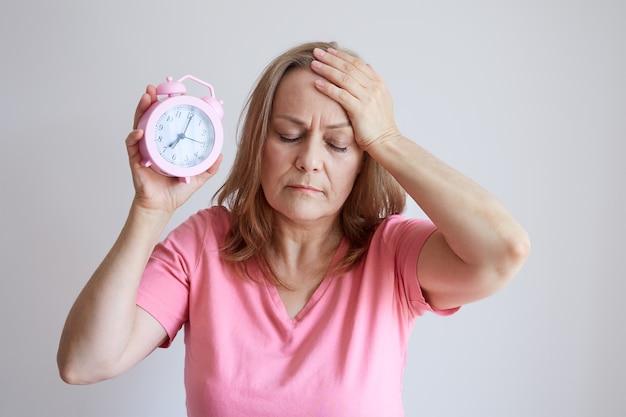 年上の女性は不眠症、頭痛に苦しんでおり、手に目覚まし時計を持っています。灰色の背景の写真。