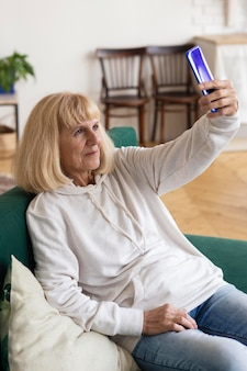 Older woman taking selfie with smartphone at home