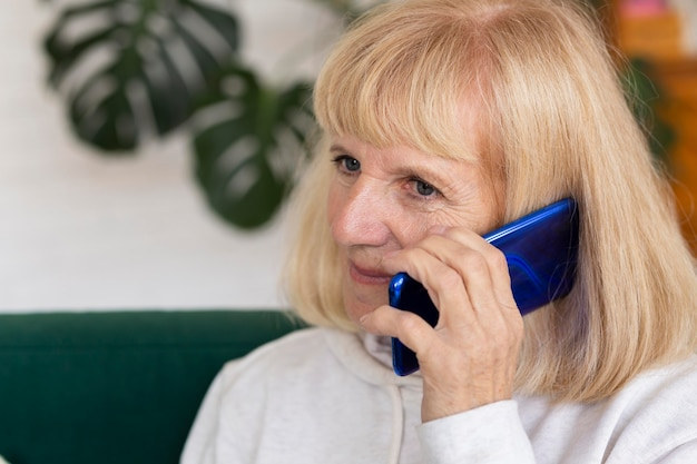 Older woman talking on the phone at home