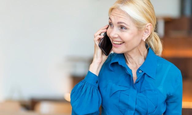 Donna anziana che parla al telefono mentre si lavora