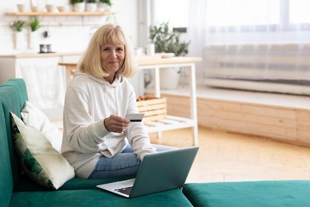 노트북과 신용 카드를 사용하여 온라인 쇼핑을하는 할머니
