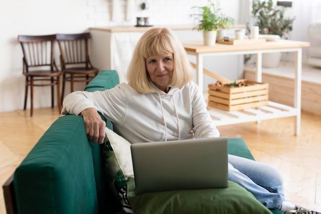 Donna anziana che utilizza computer portatile a casa