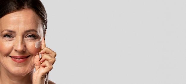 Пожилая женщина использует увлажняющий крем на лице с копией пространства