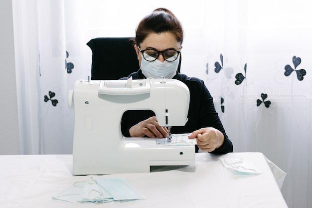 Пожилая женщина добровольно шьет маски для борьбы с вирусом. шитье на белой швейной машинке. помощь сообществу. коронавирус пандемия.