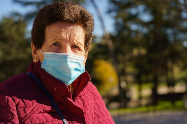 코로나 바이러스로 인해 마스크와 사회적 거리를 가진 도시 공원을 걷는 나이든 여성. 스페인.