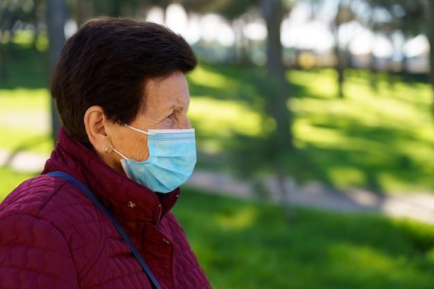 코로나 바이러스로 인해 마스크와 사회적 거리를 가진 도시 공원을 걷는 나이든 여성. 스페인. 프리미엄 사진