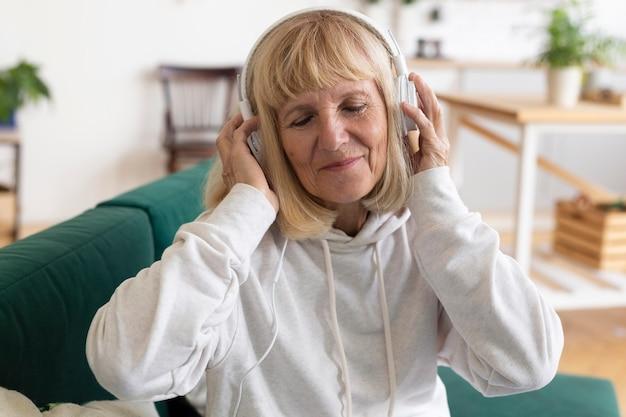 Пожилая женщина с наушниками дома, слушает музыку