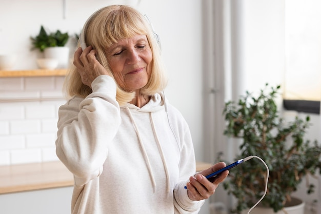 Older woman with headphones and smartphone at home