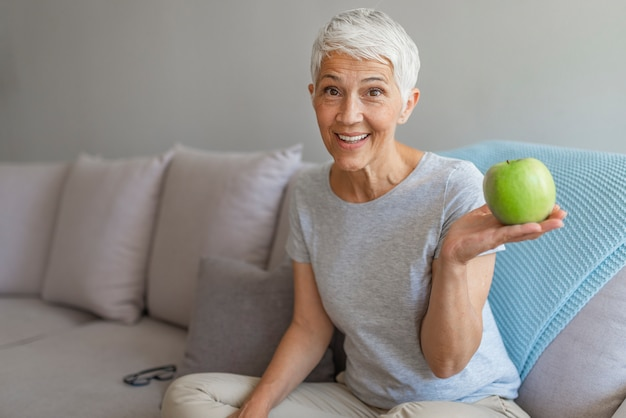 Older woman with healthy food indoors. happy senior woman with green apple at home.