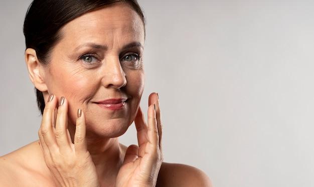 Пожилая женщина с макияжем позирует с руками на лице и копией пространства