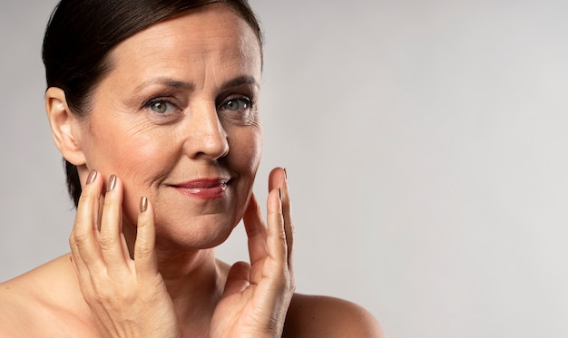 Older woman with make-up on posing with hands on face and copy space
