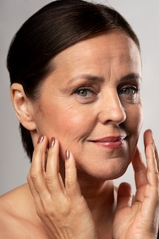 Older woman with make-up on posing with hands on face
