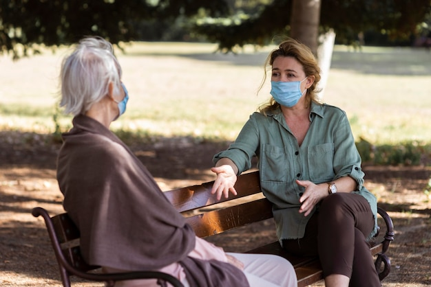 Пожилая женщина с медицинской маской разговаривает на открытом воздухе на скамейке