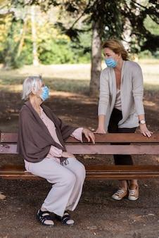 벤치에 여자와 대화하는 의료 마스크와 노인