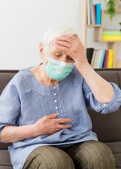 気分が悪くなる医療用マスクを持つ年上の女性