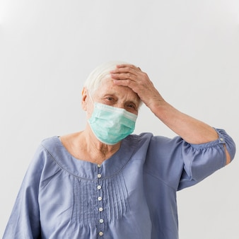 Older woman with medical mask having a fever