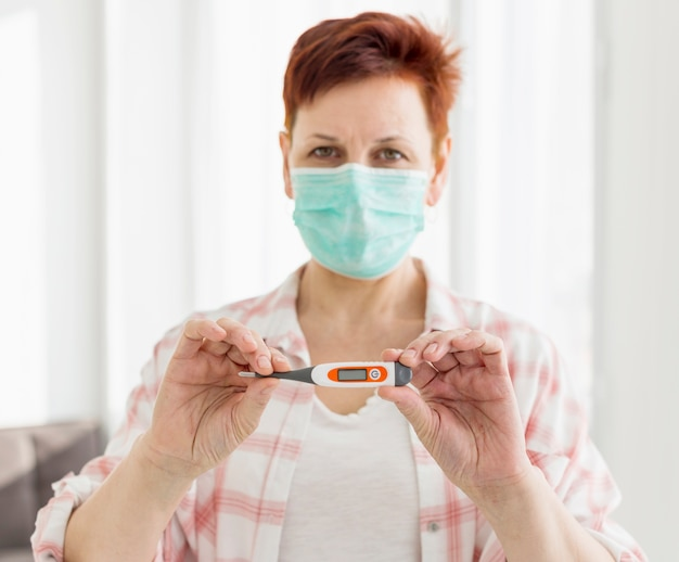 Older woman with medical mask holding up thermometer