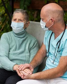 Donna anziana con mascherina medica e infermiere maschio