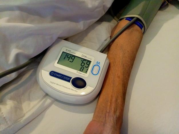 노인 여성 건강은 디지털 압력 게이지로 혈압과 심장 박동수를 확인합니다.