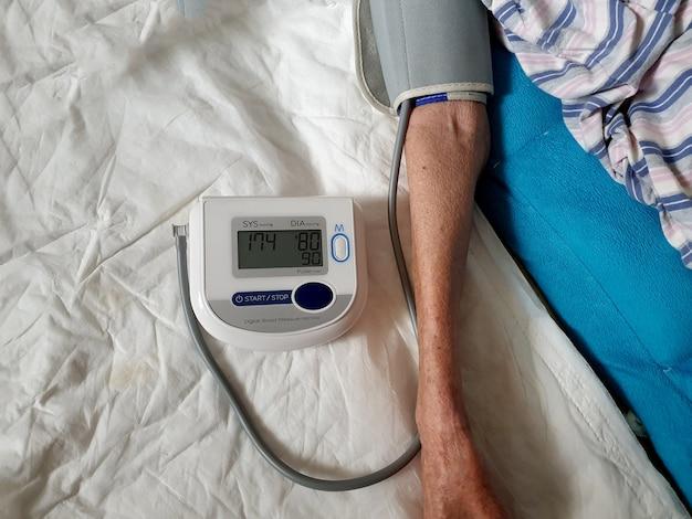 Здоровье пожилых женщин проверяет артериальное давление и частоту сердечных сокращений с помощью цифрового манометра