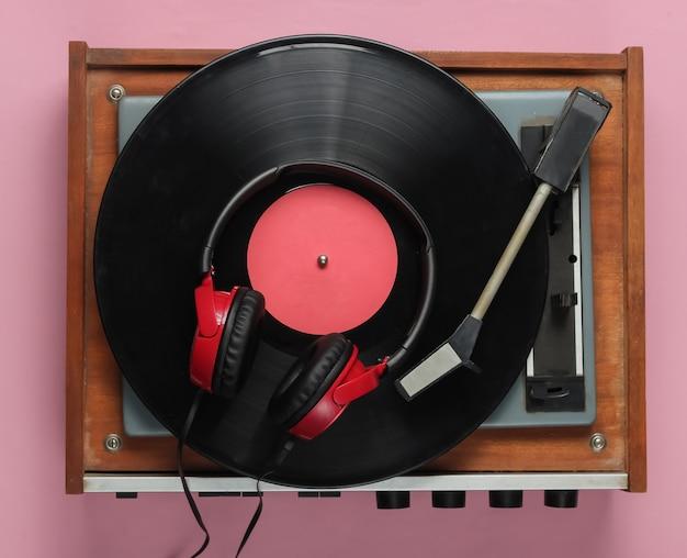 핑크 파스텔 배경에 oldfashioned 비닐 플레이어 헤드폰