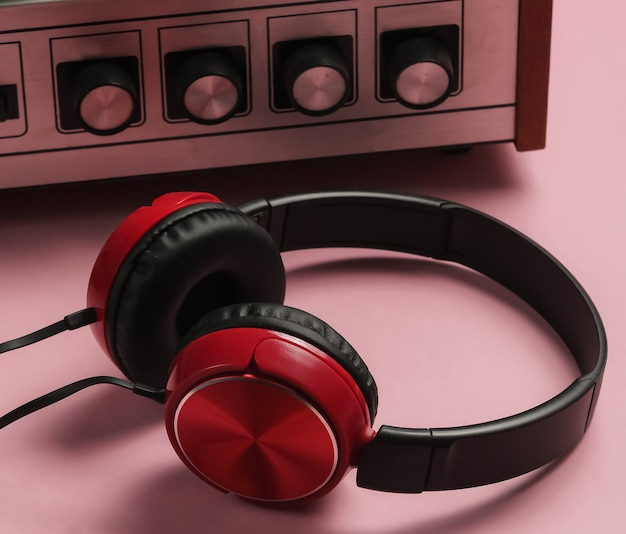 Oldfashioned vinyl player headphones on pink pastel background
