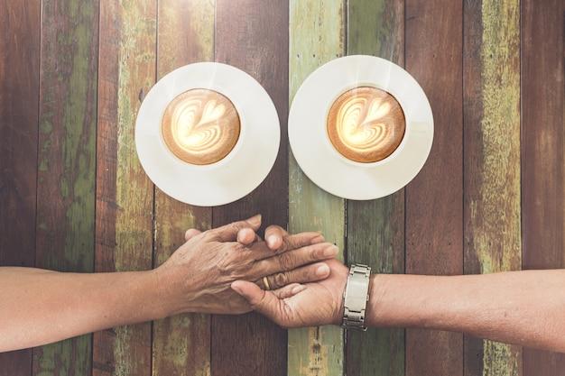 コーヒーショップでoleカップルの手の愛